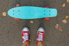 Fermez-vous des pieds et du panneau bleu de patin de penny avec les roues roses Photo stock