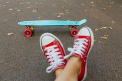 Fermez-vous des pieds et du panneau bleu de patin de penny avec les roues roses Photo libre de droits