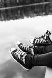 Fermez-vous des pieds masculins et femelles du ` s détendant par le lac Photographie stock