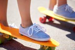 Fermez-vous des pieds montant des planches à roulettes sur la rue de ville Image libre de droits