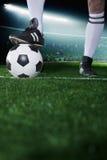 Fermez-vous des pieds sur le ballon de football, nuit dans le stade Photographie stock libre de droits