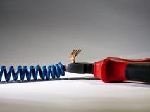 Fermez-vous des pinces rouges et du fil tordu bleu sur le fond blanc Pinces coupant le câble images stock