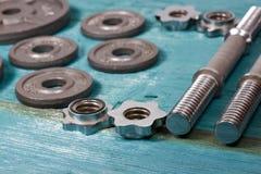 Fermez-vous des plats métalliques de poids sur le plancher en bois et des haltères à l'arrière-plan Image stock