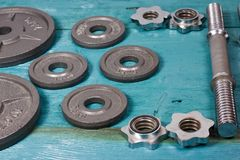 Fermez-vous des plats métalliques de poids sur le plancher en bois et des haltères à l'arrière-plan Photo stock