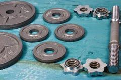 Fermez-vous des plats métalliques de poids sur le plancher en bois et des haltères à l'arrière-plan Images libres de droits