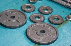 Fermez-vous des plats métalliques de poids sur le plancher en bois et des haltères à l'arrière-plan Photos stock