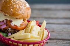Fermez-vous des pommes frites et du cheeseburger dans le panier image stock