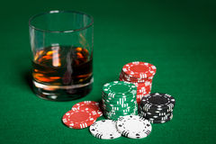 Fermez-vous des puces de casino et du verre de whiskey sur la table Image libre de droits
