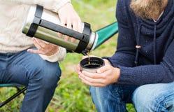 Fermez-vous des randonneurs versant le thé du thermos dans la tasse Photos libres de droits
