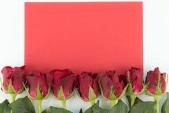 Fermez-vous des roses rouges sur un fond en bois avec le message vide Photographie stock