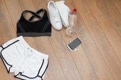 Fermez-vous des sports de femelle habillement, espadrilles, smartphone, écouteurs et bouteille Photos libres de droits