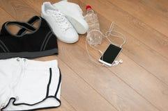 Fermez-vous des sports de femelle habillement, espadrilles, smartphone, écouteurs et bouteille Photographie stock