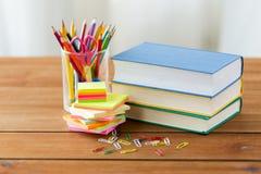 Fermez-vous des stylos, des livres, des agrafes et des autocollants Photo stock
