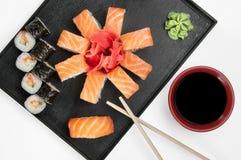 Fermez-vous des sushi de sashimi r?gl?s avec les baguettes et le soja sur un plateau servant images stock