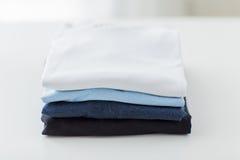 Fermez-vous des T-shirts repassés et pliés sur la table Photographie stock