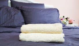 Fermez-vous des toiles bleues d'auberge et de la serviette de bain se trouvant sur le lit Service h?telier et fond propre de cham images stock