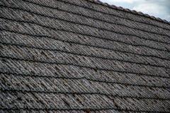 Fermez-vous des tuiles de toiture âgées sur la vieille maison dans le village Beaucoup de mousse sur le toit carrelé du taudis Sc photo libre de droits