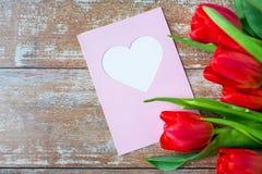 Fermez-vous des tulipes et de la carte de voeux avec le coeur Images stock