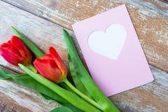 Fermez-vous des tulipes et de la carte de voeux avec le coeur Photos libres de droits