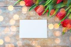 Fermez-vous des tulipes rouges et du papier blanc ou marquez avec des lettres Photo libre de droits