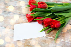 Fermez-vous des tulipes rouges et du papier blanc ou marquez avec des lettres Images stock