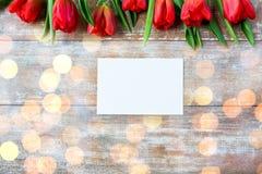 Fermez-vous des tulipes rouges et du papier blanc ou marquez avec des lettres Image libre de droits