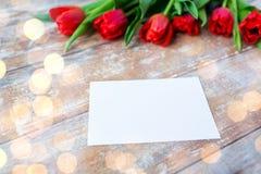 Fermez-vous des tulipes rouges et du papier blanc ou marquez avec des lettres Photographie stock