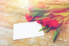 Fermez-vous des tulipes rouges et du papier blanc ou marquez avec des lettres Photos stock