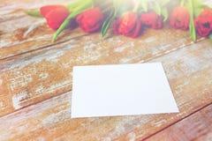 Fermez-vous des tulipes rouges et du papier blanc ou marquez avec des lettres Photos libres de droits
