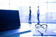 Fermez-vous des verres d'oeil sur le bureau de travail avec le diagramme et l'ordinateur portable sur le lieu de travail d'affair Photos stock