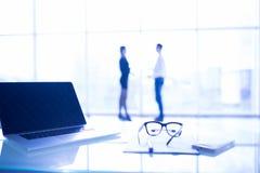 Fermez-vous des verres d'oeil sur le bureau de travail avec le diagramme et l'ordinateur portable sur le lieu de travail d'affair Photo libre de droits