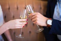 Fermez-vous des verres de champagne dans des mains masculines et femelles Photo stock