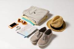 Fermez-vous des vêtements d'été et de la carte de voyage sur la table Image stock