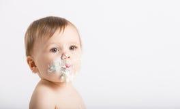 Fermez-vous du bébé avec le visage plein du gâteau et du givrage Photographie stock libre de droits