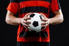 Fermez-vous du ballon de football dans des mains de l'athlète Photographie stock