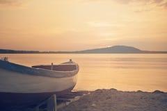 Fermez-vous du bateau bleu en bois sur la plage Regard de filtre de vintage Image libre de droits
