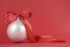 Fermez-vous du bel ornement d'arbre de Noël blanc avec le ruban rouge de point de polka sur le fond rouge Image libre de droits