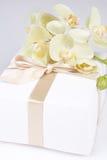 Fermez-vous du boîte-cadeau avec le ruban et l'orchidée blanche Photographie stock libre de droits