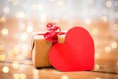 Fermez-vous du boîte-cadeau et de la note en forme de coeur sur le bois Images stock