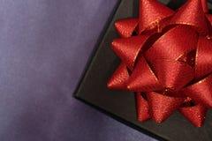 Fermez-vous du boîte-cadeau noir sur le tissu foncé photographie stock