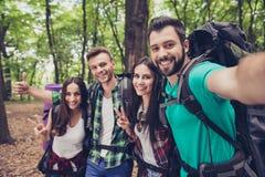 Fermez-vous du bois gentil gai de quatre amis au printemps, embr Photos stock