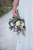 Fermez-vous du bouquet rustique dans la main de sa jeune mariée Image libre de droits