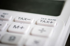 Fermez-vous du bouton d'impôts sur la calculatrice de blanc d'affaires Photos stock