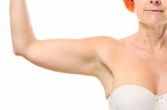 Fermez-vous du bras d'une femme plus âgée avec les cheveux rouges Photographie stock