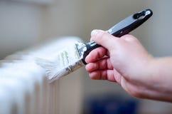 Fermez-vous du bras de peintre peignant un radiateur de chauffage avec le rouleau de peinture Main professionnelle d'ouvrier tena Photo libre de droits