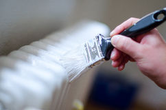 Fermez-vous du bras de peintre peignant un radiateur de chauffage avec le rouleau de peinture Main professionnelle d'ouvrier tena Photos stock