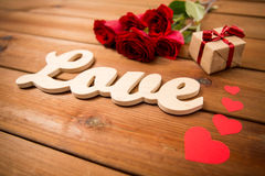 Fermez-vous du cadeau, de l'amour de mot, des roses rouges et des coeurs Photographie stock