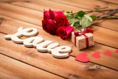 Fermez-vous du cadeau, de l'amour de mot, des roses rouges et des coeurs Photo stock