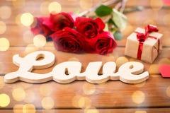Fermez-vous du cadeau, de l'amour de mot, des roses rouges et des coeurs Images libres de droits