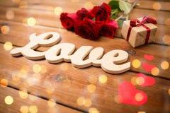 Fermez-vous du cadeau, de l'amour de mot, des roses rouges et des coeurs Image libre de droits